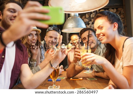 people, leisure, friendship, technology and communication concept - group of happy smiling friends with smartphone and drinks taking selfie at bar or pub