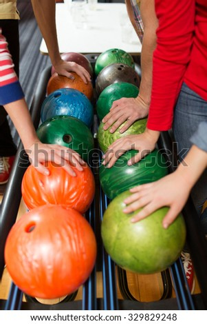 people, leisure, sport and entertainment concept - close up of players hands and ball return system in bowling club - stock photo