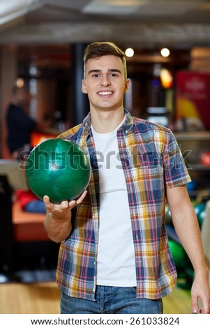 people, leisure, sport and entertainment concept - happy young man holding ball in bowling club