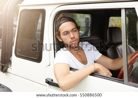 People, leisure, travel and vacations concept. Fashionable unshaven man wearing snapback driving his white crossover utility vehicle while trying to get around traffic jam, going on safari trip