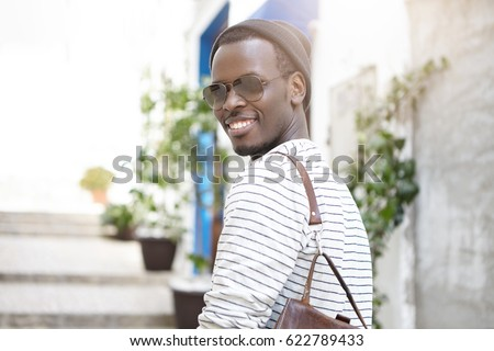 People, lifestyle, leisure, tourism and travel. Outdoor shot of dark-skinned male student smiling broadly, enjoying good sunny day walking on streets of European city, wearing stylish clothes