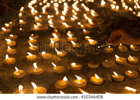 People light candle to pay respect to buddha relic at buddhist temple - stock photo