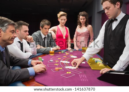 People looking at dealer dealing blackjack cards in the casino