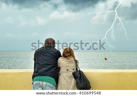 people looking the sea with cloudy sky in winter