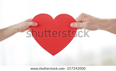 people, love, charity and family concept - close up of child and male hands holding red heart shape at home - stock photo