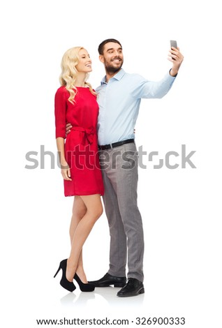 people, love, couple, technology and holidays concept - happy young woman and man taking selfie with smartphone and hugging