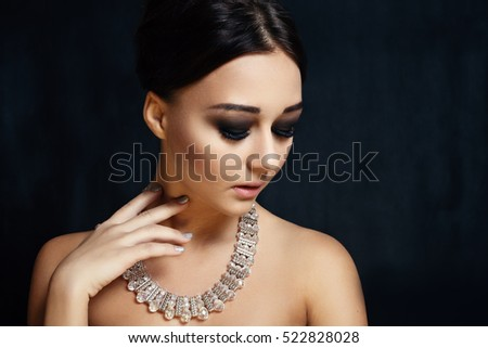 people, luxury, jewelry and fashion concept - Fashion portrait of young beautiful lady with earring on black background
