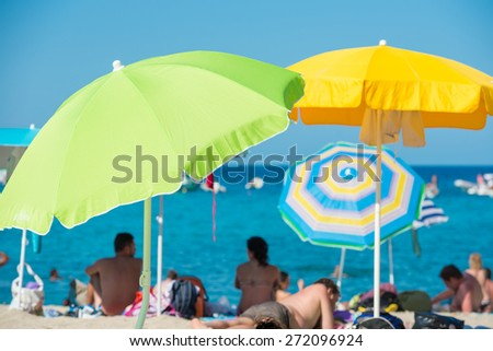 People lying under colorful umbrellas on the tropical beach with blue sea as background - stock photo