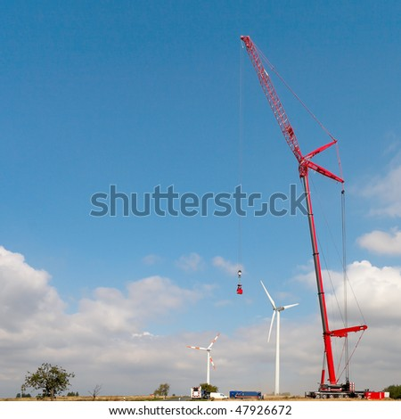 People make repairs wind turbines with the help of a crane - stock photo