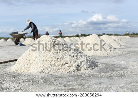 People making a pile of salt in the salt pan in Thailand - stock photo