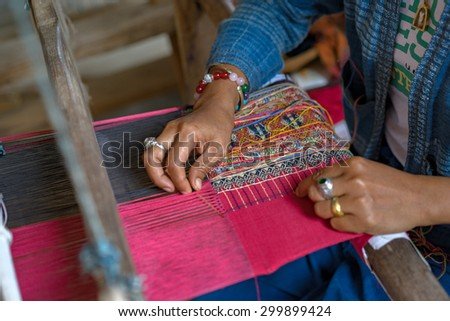 People making cotton textile pattern from interweave thread.