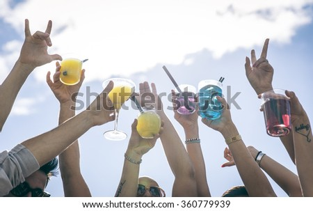People making party and dancing on a beach party. Holding cocktails and pointing to the sky.