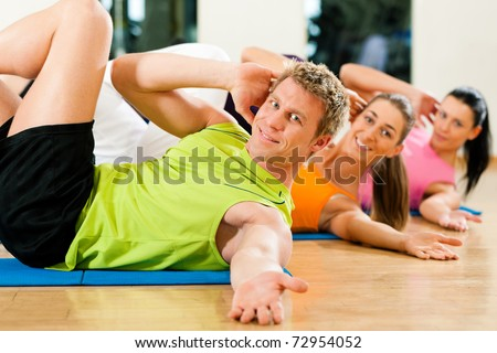 People, man and women, exercising doing sit-ups in gym or fitness club - stock photo