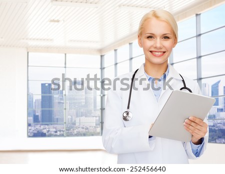 people, medicine and profession concept - smiling young female doctor with tablet pc computer and stethoscope over clinic background - stock photo