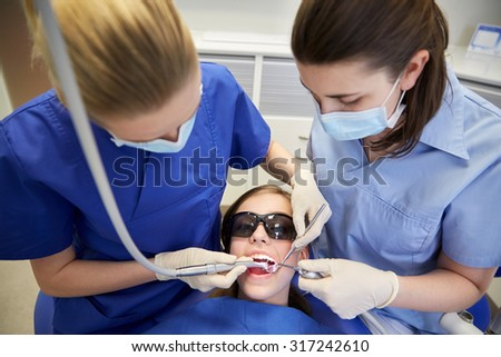 people, medicine, stomatology and health care concept - female dentists with mirror, drill and probe treating patient girl teeth at dental clinic office - stock photo