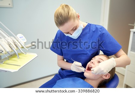 people, medicine, stomatology and health care concept - happy female dentist with mirror and probe checking patient girl teeth up at dental clinic office - stock photo