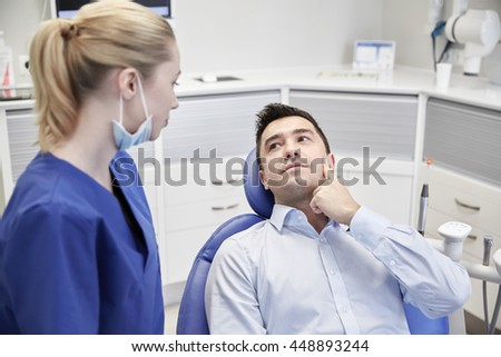 people, medicine, stomatology and health care concept - woman patient talking to male dentist and complain of toothache at dental clinic office - stock photo