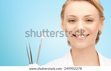 people, medicine, stomatology and healthcare concept - happy young female dentist with tools over blue background - stock photo