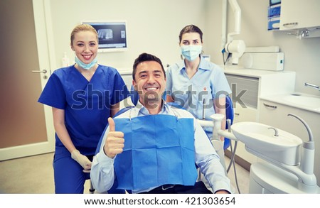 people, medicine, stomatology, gesture and health care concept - happy female dentist with assistant and man patient showing thumbs up at dental clinic office - stock photo