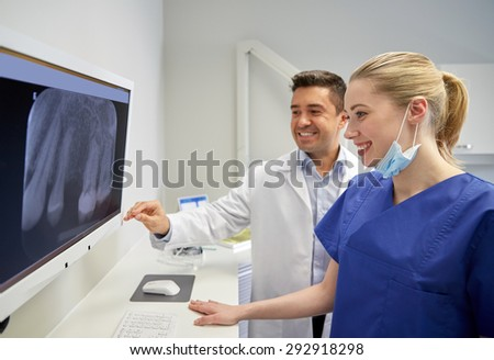 people, medicine, stomatology, technology and health care concept - happy dentists looking to x-ray scan on monitor at dental clinic - stock photo