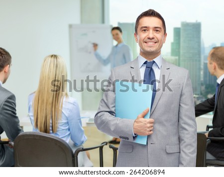 people, meeting and work concept - happy smiling businessman in suit holding open folder over business team in office background - stock photo