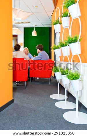 People, meeting informally during a project team get together in the comfortable lobby of a modern office building - stock photo