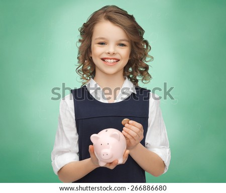 people, money, finances and savings concept - happy girl holding piggy bank and coin over green chalk board background