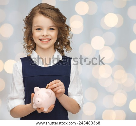 people, money, savings, investment and children concept - smiling girl putting coin into piggy bank over holidays lights background