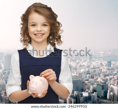 people, money, savings, investment and children concept - smiling girl putting coin into piggy bank over city background - stock photo