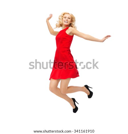 people, motion, happiness and holidays concept - happy young woman in red dress jumping high in air - stock photo