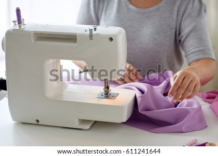 people, needlework and tailoring concept - tailor woman with sewing machine stitching fabric at studio