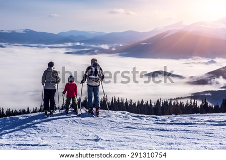 People observing mountain scenery. Family of three people stays in front of scenic landscape. These are skiers, they dressed in winter sport jackets and have skies attached. - stock photo