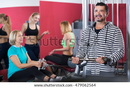 People of different age having strength training in gym