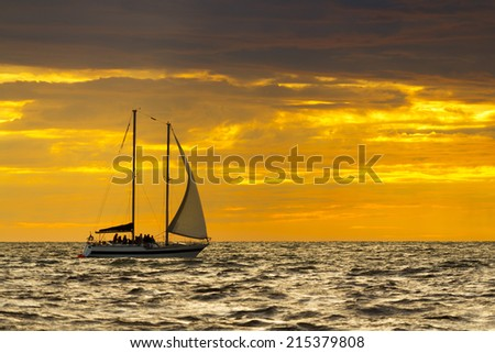 People on a sailboat at sunset.