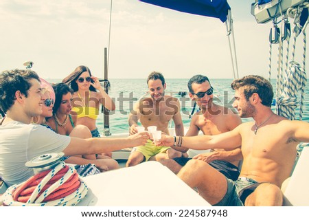 People on a yacht - Group of friends toasting drinks and having party on a sailing boat - Tourists on vacation - stock photo