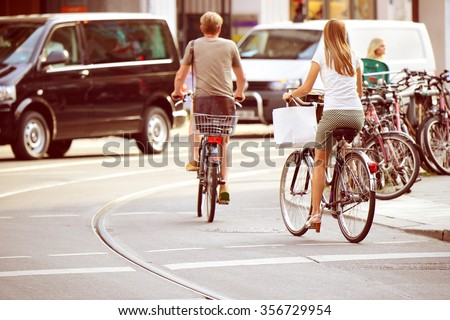 People on bikes in traffic - stock photo