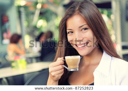 People on cafe - woman drinking coffee smiling at camera. Beautiful interracial Asian / Caucasian young woman enjoying typical spanish coffee called cortado.