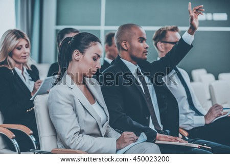 People on conference. Group of business people in formalwear sitting at the chairs in conference hall and writing something gin their note pads while handsome African man raising his arm - stock photo