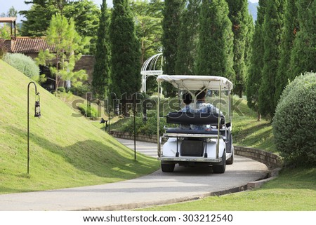 People on Golf cart in park.