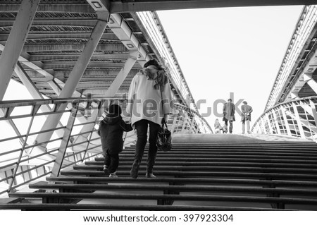 People on pedestrian Solferino bridge over Seine River near Orsey's Museum. Paris, France. Back view. - stock photo