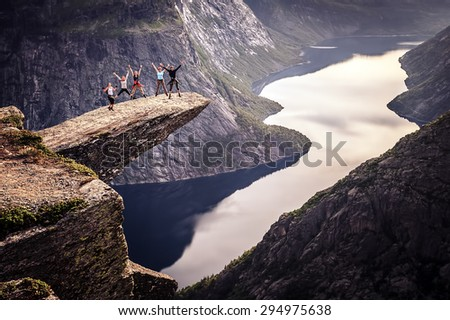 People on rocks harsh Norway, Trolltunga - stock photo