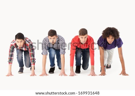 People on starting line. Group of young multi-ethnic men standing on starting line and looking forward while isolated on white - stock photo