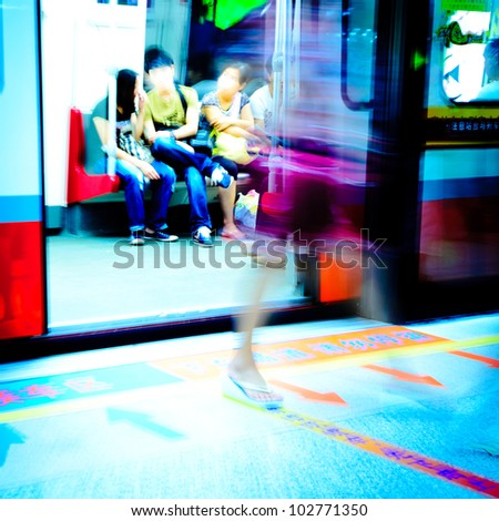 people on subway platform leaving the train, blurred motion - stock photo