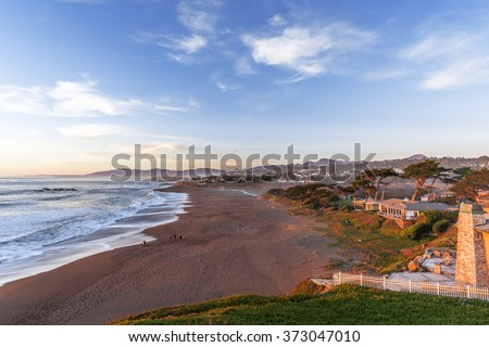 People on the beach, blue sky and sea, waves crashing at sunset on Moonstone Beach next to Shamel Park and Santa Rosa Estuary, along Big Sur Coast, California Central Coast, near Cambria CA. - stock photo