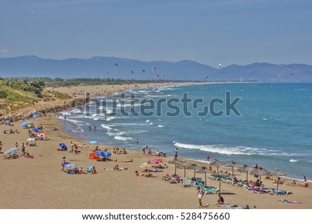 People on the beach with views of the mountains