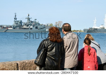 People on the boardwalk watching the Russian naval fleet - stock photo