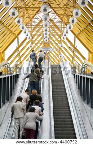 People on the escalator of pedestrian bridge - stock photo