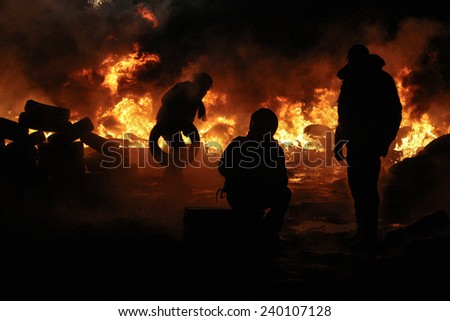People on the fire take part in a clash at the Grushevskogo street during anti-government protest in Kiev, Ukraine, January 25, 2014