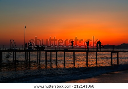 people on the pier during the sunset  - stock photo