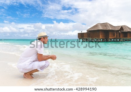 People on the shore enjoying the exotic view of sitting - stock photo